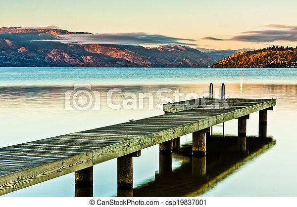 Scenic Dock on Mountain Lake at Sunrise - csp19837001