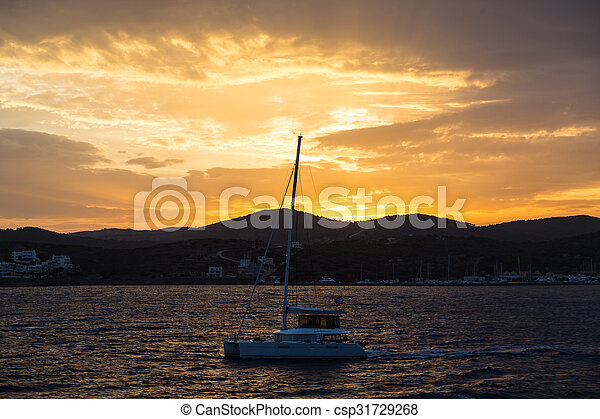 Scenic view of a beautiful sunset over the sea with boat on water - csp31729268