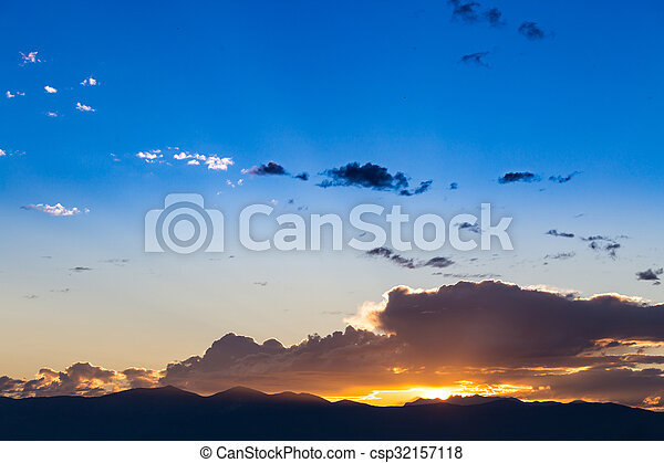 Scenic view of a beautiful sunset with blue sky and clouds over the mountains - csp32157118