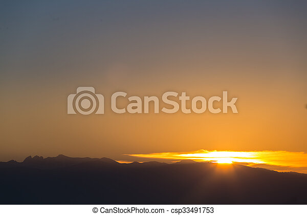 Scenic view of a beautiful sunset with clear sky over the mountains - csp33491753