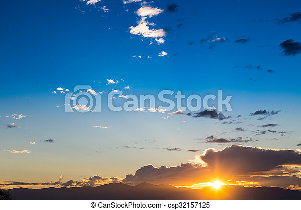 Scenic view of a beautiful sunset with blue sky and clouds over the mountains - csp32157125