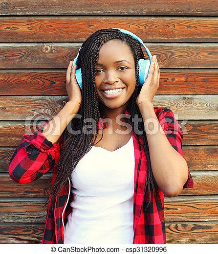 schöne , stadt, frau, hölzern, aus, kopfhörer, musik, hintergrund, afrikanisch, spaß, lächeln, haben, hört - csp31320996