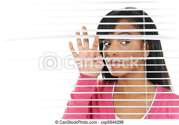Eine Frau, die durch venetianische Jalousien schaut - csp5944298