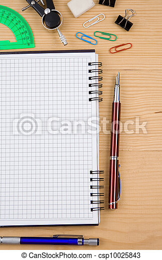school accessories and checked notebook on wood - csp10025843