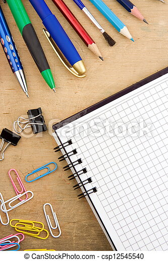 school accessories and checked notebook on wood - csp12545540