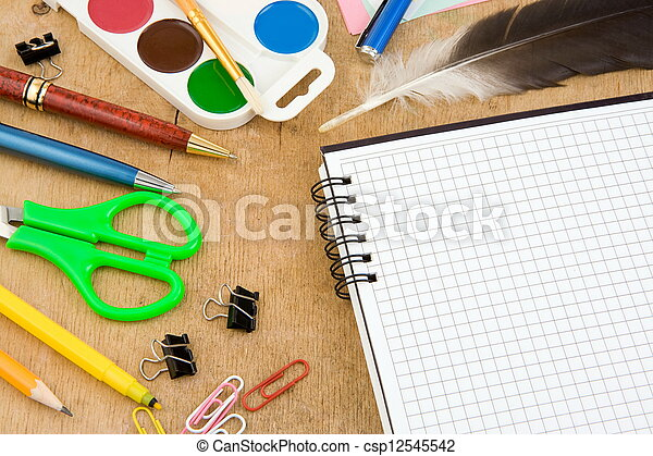 school accessories and checked notebook on wood - csp12545542