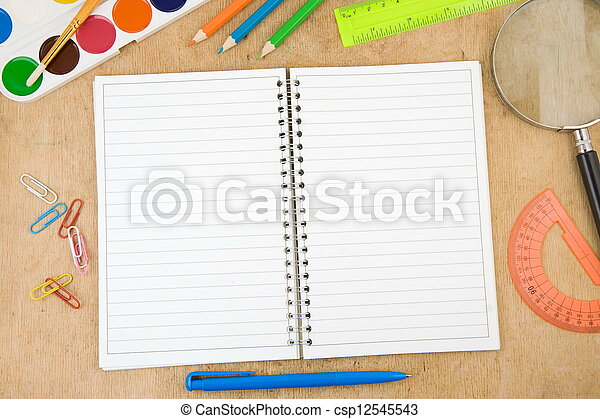 school accessories and checked notebook on wood - csp12545543