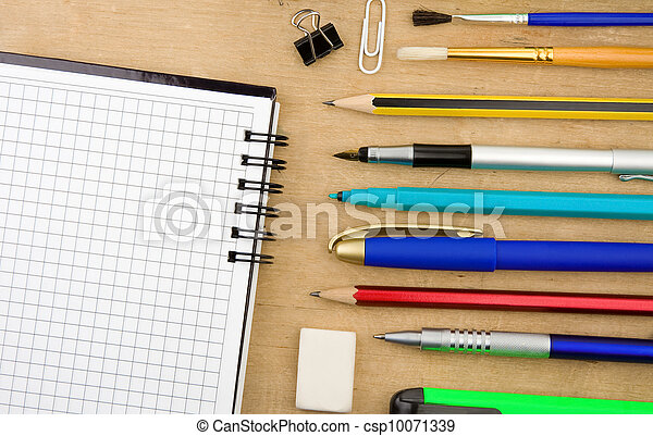 school accessories and checked notebook on wood - csp10071339