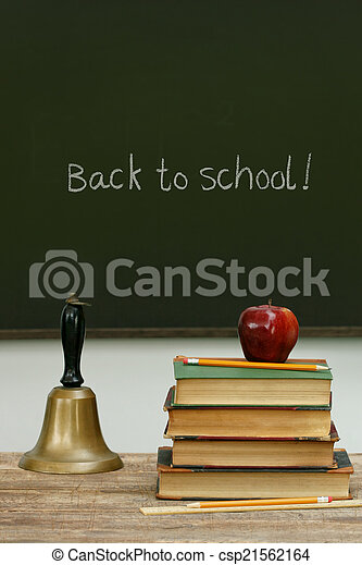 School bell and books on desk with chalkboard - csp21562164