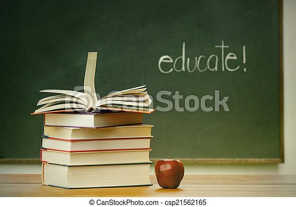 School books and apple on desk - csp21562165