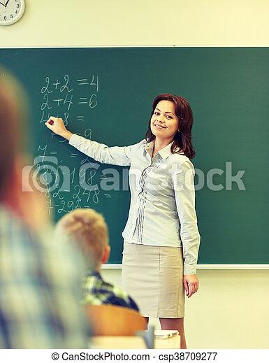 school kids and teacher writing on chalkboard education elementary