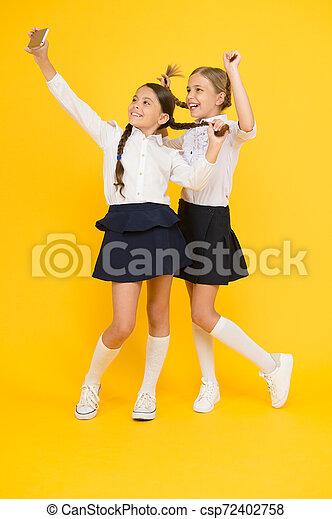 Descanso escolar. Día de conocimiento. Amigos felices con smartphone. Los niños hacen fotos de selfie, amistad. Niñas con uniforme escolar. De vuelta a la escuela. Un blog educativo. Tecnología digital. Educación online - csp72402758