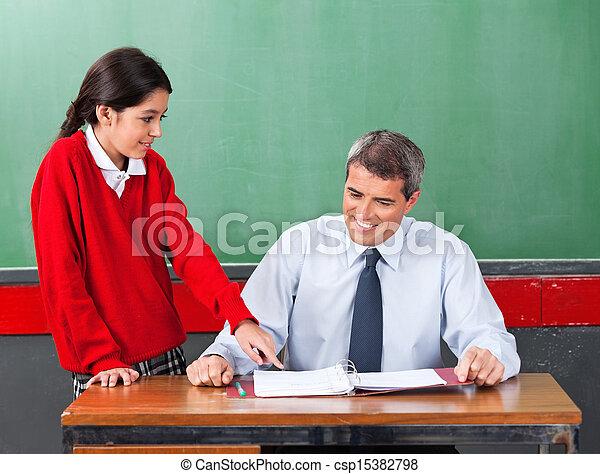 Schoolgirl Asking Question To Teacher At Desk Csp15382798