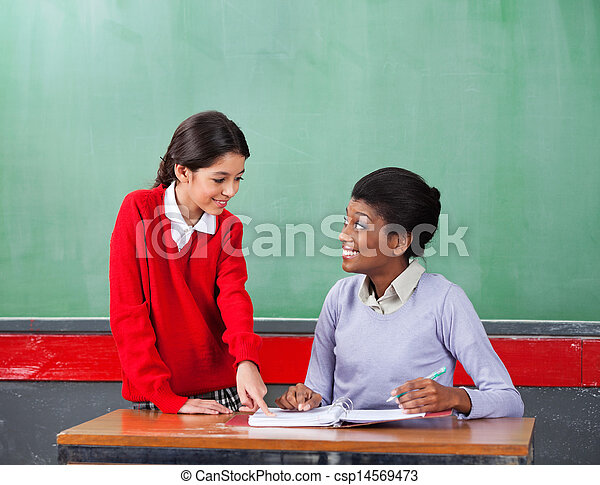 Schoolgirl Pointing On Paper While Teacher Looking At Her Csp14569473