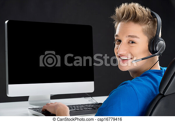 Gamer. Rear view of Teenager boy playing video games at his computer and look over shoulder - csp16779416