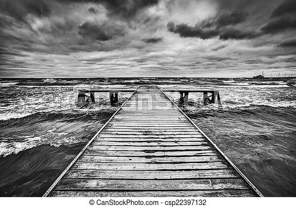 Altes Holzdüsen im Sturm auf dem Meer. Dramatische Himmel mit dunklen, schweren Wolken - csp22397132