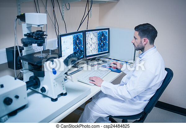 Science student looking at microscopic images - csp24484825