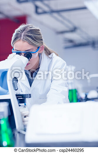 Science student looking through microscope in the lab - csp24460295