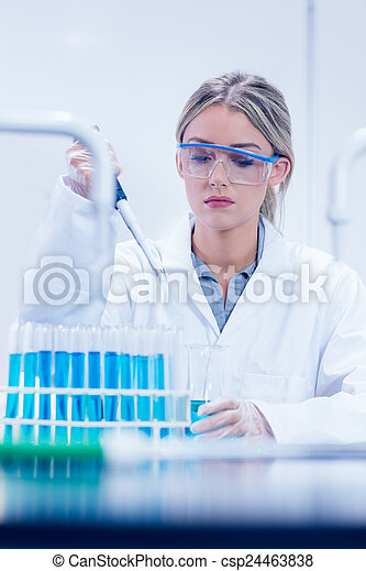 Science student using pipette in the lab - csp24463838