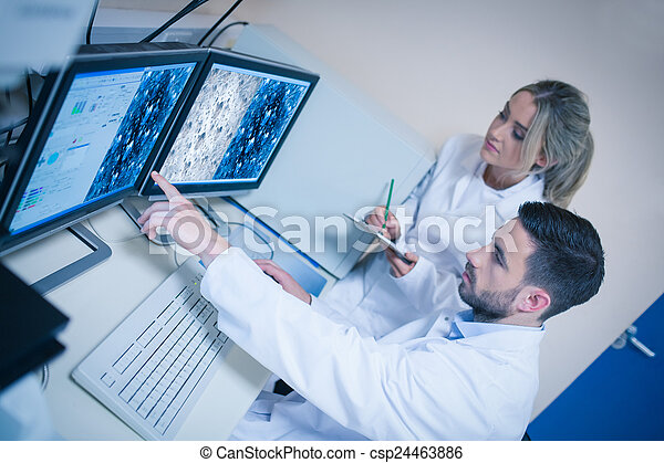 Science students looking at microscopic images - csp24463886