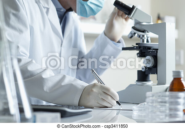 Scientist conducting research with microscope  - csp3411850