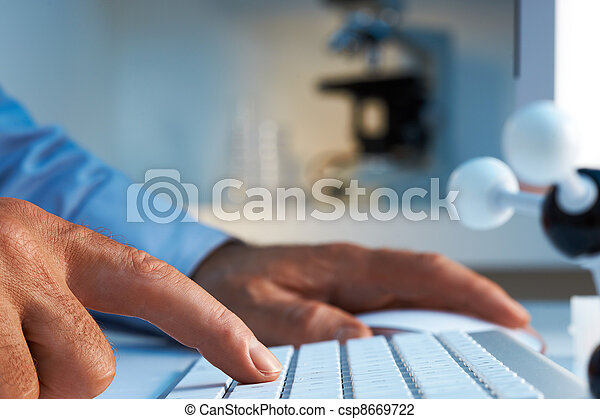 Scientist entering data into computer - csp8669722