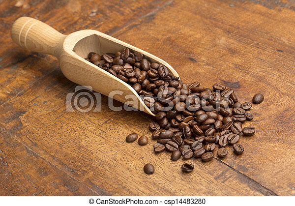 scoop with coffee beans on wooden table - csp14483280