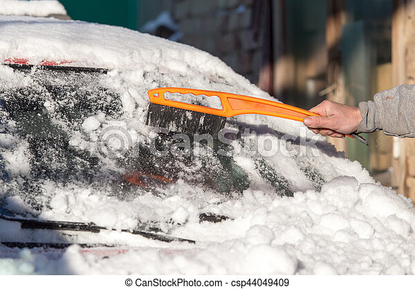 scraping snow from car winter - csp44049409