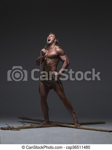Screaming muscular man, hands tied rope to wooden beams. Screaming ...