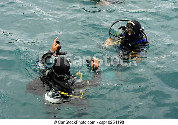 scuba divers scuba dive in sea - csp10254198