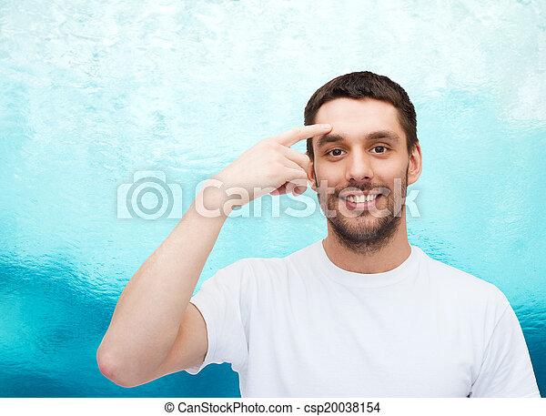 Un joven guapo sonriente apuntando a la frente - csp20038154