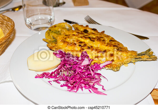 Sea bass on a bed of potatoes with almonds - csp45210771