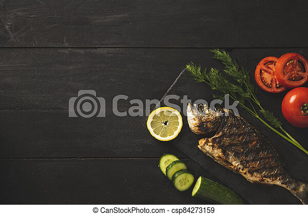 Sea bream on a black wooden background with vegetables - csp84273159