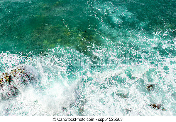 Sea waves break up on the stones of the coast. The raging sea and foam. View from above. Green background. - csp51525563