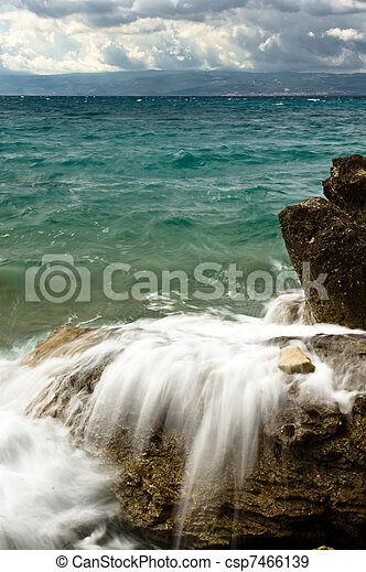 Sea waves on the rocks. Stormy weather. - csp7466139