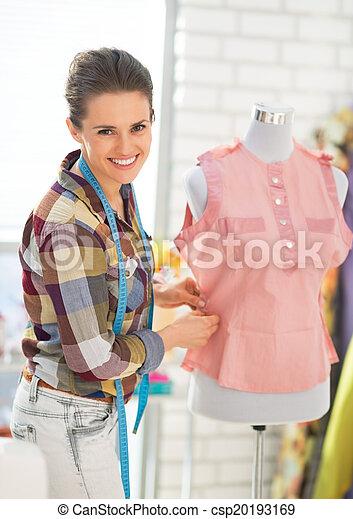 Seamstress adjusting clothing on mannequin - csp20193169