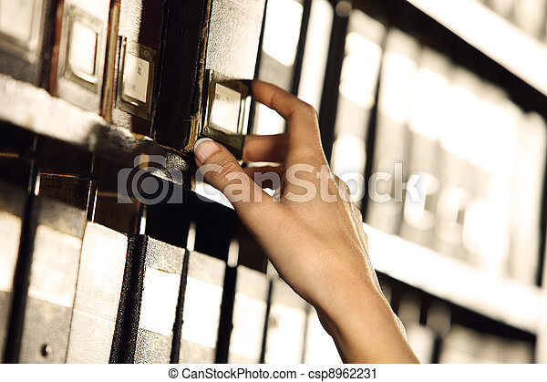 Searching in archives. Student hands searching from a filling cabinet.  - csp8962231