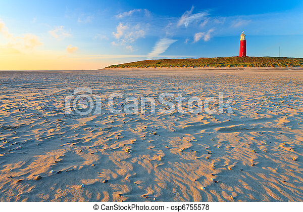 Seaside with sand dunes and lighthouse at sunset - csp6755578