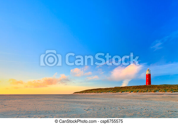 Seaside with sand dunes and lighthouse at sunset - csp6755575