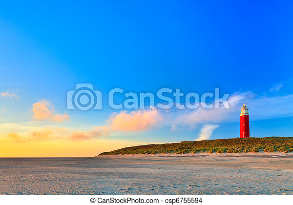 Seaside with sand dunes and lighthouse at sunset - csp6755594