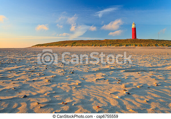 Seaside with sand dunes and lighthouse at sunset - csp6755559