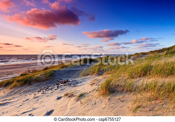 Seaside with sand dunes at sunset - csp6755127