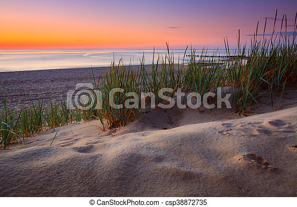 Seaside with tuft of grass, sand dunes and colorful sky at sunset. - csp38872735