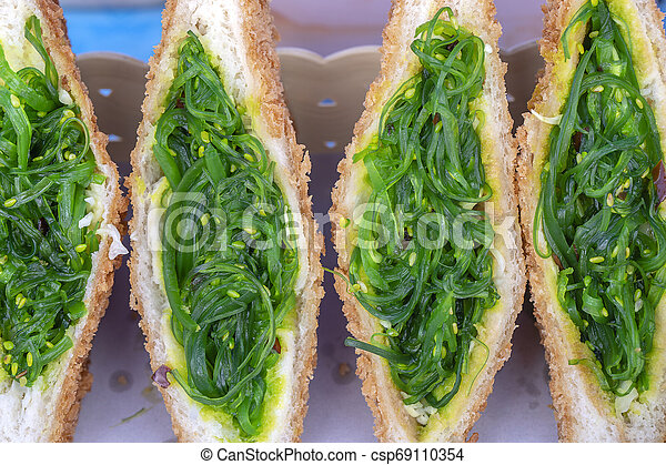 Seaweed salad sandwich for sell at street food market in Thailand, close up. Tasty green seaweed salad sandwich close up - csp69110354