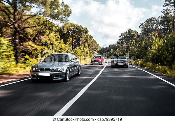 Sedan cars driving on the forest road - csp79395719