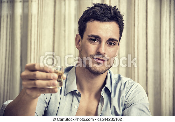 Seductive handsome young man sitting drinking - csp44235162