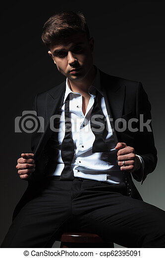76021da6ebf2 seductive man with undone bowtie holding tuxedo collar while sitting -  csp62395091