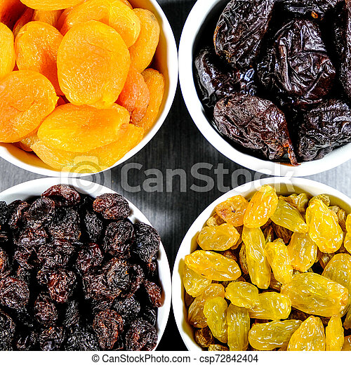 Selection of Healthy Dried Fruits In White Bowls - csp72842404