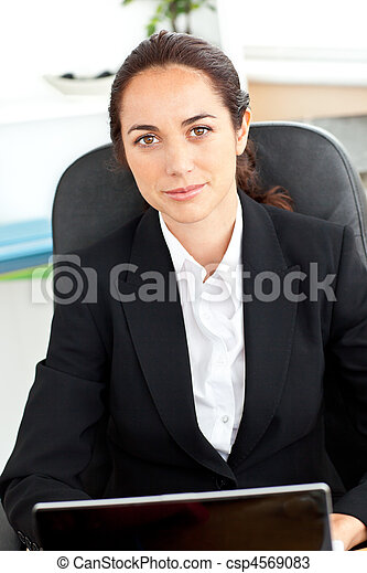Self-assured hispanic businesswoman sitting at her desk in front of her laptop in her office - csp4569083
