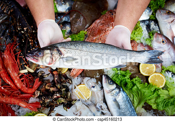 Seller presenting a fresh sea bass fish in fish store - csp45160213